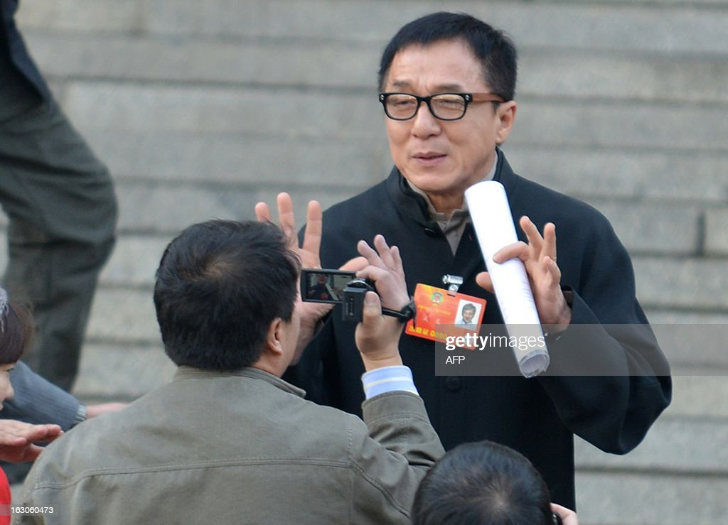 This picture taken on March 3, 2013 shows Hong Kong movie star Jackie Chan (R) stopped by a journalist as he attends the opening session of the Chinese People's Political Consultative Conference (CPPCC) at the Great Hall of the People in Beijing. Thousands of delegates from across China meet this week to seal a power transfer to new leaders whose first months running the Communist Party have pumped up expectations with a deluge of propaganda. CHINA