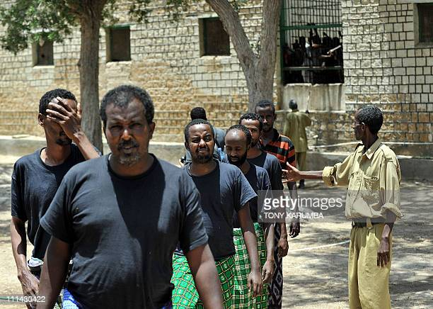 This picture taken on March 30 2011 shows Somali men convicted of piracy being directed across a yard by a warder at the Berbera prison in Somalia's...