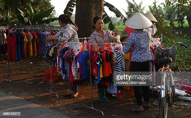 This picture taken on March 30 2015 shows women selling clothes at their roadside stands in Quoc Oai district on the outskirts of Hanoi AFP PHOTO /...