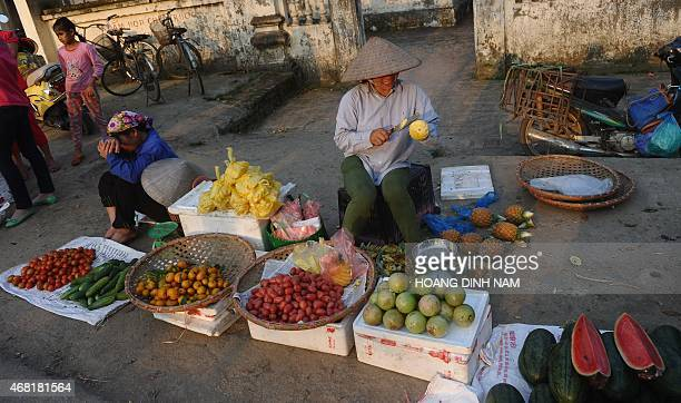 This picture taken on March 30 2015 shows women selling fruits at a village's afternoon market in Quoc Oai district on the outskirts of Hanoi Local...