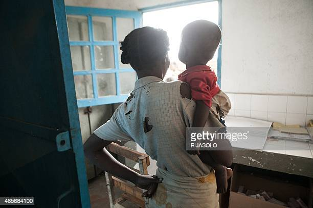 This picture taken on March 4 2015 shows an undernourished 15monthold baby and his mother waiting for medications in the village of Imongy in the...