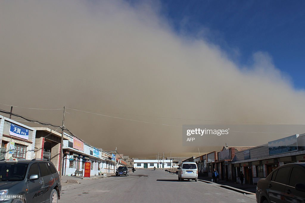This picture taken on March 5, 2013 shows a sandstorm hitting the town of Shandan Horse Ranch in Zhangye, northwest China's Gansu province. According to eyewitnesses, large amounts of black dust and sand were pushed by strong winds, resembling a wall rolling across the horse farm from the west. CHINA