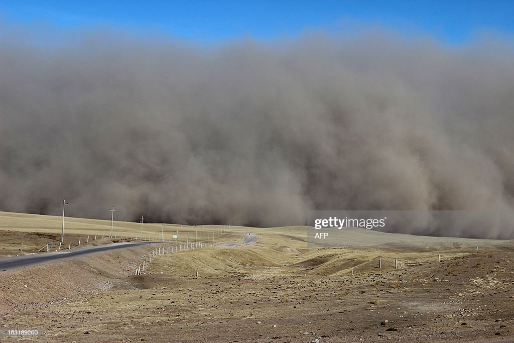 This picture taken on March 5, 2013 shows a sandstorm hitting the town of Shandan Horse Ranch in Zhangye, northwest China's Gansu province. According to eyewitnesses, large amounts of black dust and sand were pushed by strong winds, resembling a wall rolling across the horse farm from the west. CHINA OUT AFP PHOTO