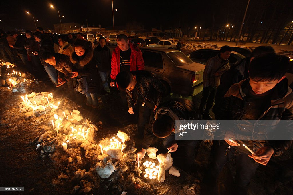 This picture taken on March 5, 2013 shows Changchun citizens gathered together to mourn the death of a two-month-old baby killed by a car thief in Changchun, northeast China's Jilin province. The thief strangled the baby to death after stealing a vehicle with the infant inside, police said, provoking outrage across the country on March 5, 2013. CHINA OUT AFP PHOTO