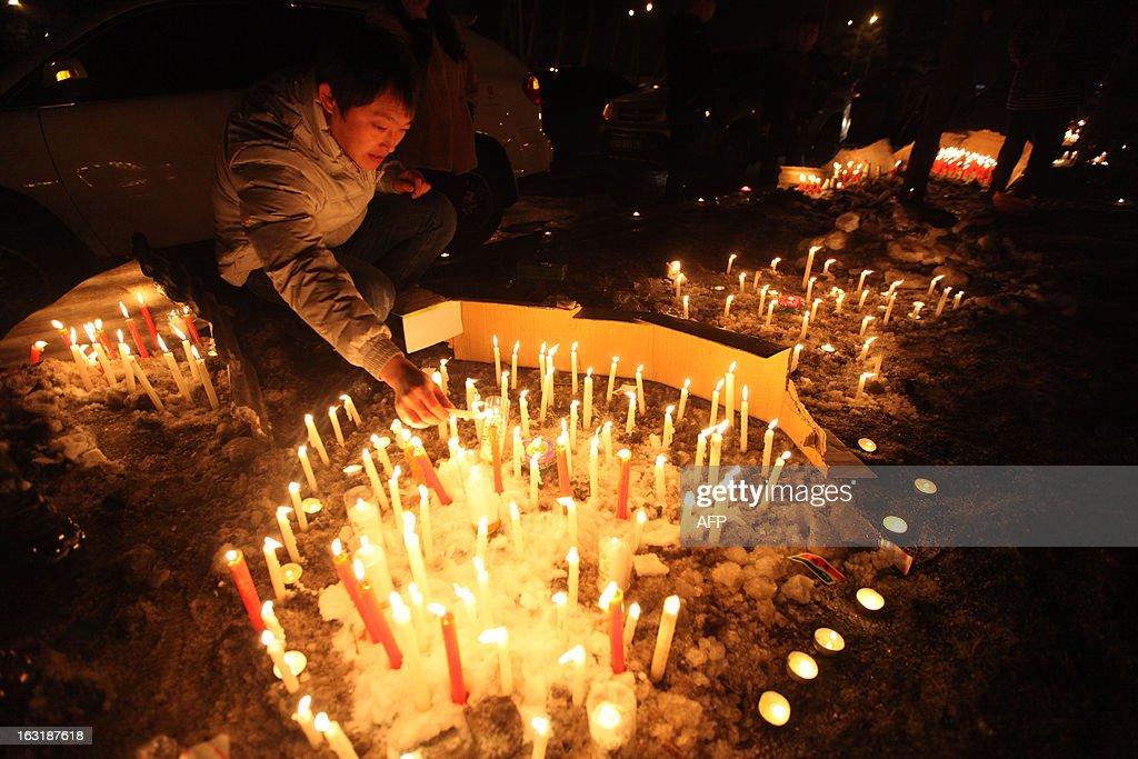 This picture taken on March 5, 2013 shows Changchun citizens gathered together to mourn the death of a two-month-old baby killed by a car thief in Changchun, northeast China's Jilin province. The thief strangled the baby to death after stealing a vehicle with the infant inside, police said, provoking outrage across the country on March 5, 2013. CHINA
