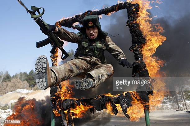 This picture taken on March 5 2014 shows a soldier jumping over a ring of fire during a tactical training mission in Heihe northeast China's...