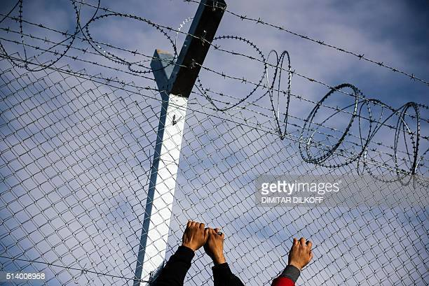 This picture taken on March 6 2016 shows the hands of two migrants men clinging to a razortopped fence close to the gate at the GreekMacedonian...