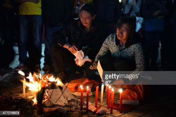 This picture taken on March 7 2014 shows mourners burning joss money and incenses at the scene of the terror attack at the main train station in...