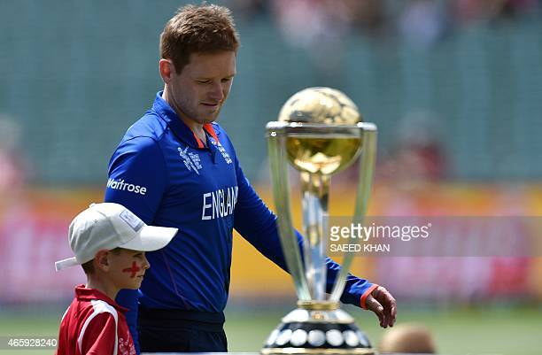 This picture taken on March 9 2015 shows England's cricket team captain Eoin Morgan walks past the Cricket World Cup trophy prior to the 2015 Cricket...