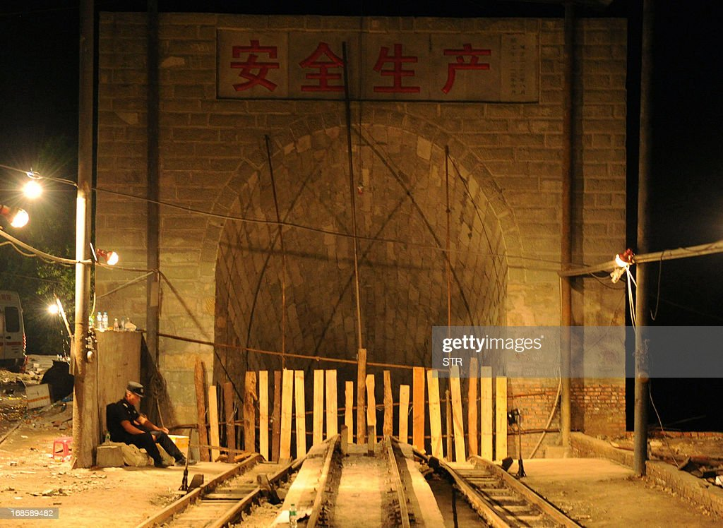 This picture taken on May 11, 2013 shows a rescuer sitting at the entrance of Taozigou mine in Luzhou city, Sichuan Province. An accidental explosion at a coal mine in southwest China killed 27 miners on May 11, state media said, in the second deadly incident to hit the country's troubled industry in as many days. CHINA OUT AFP PHOTO