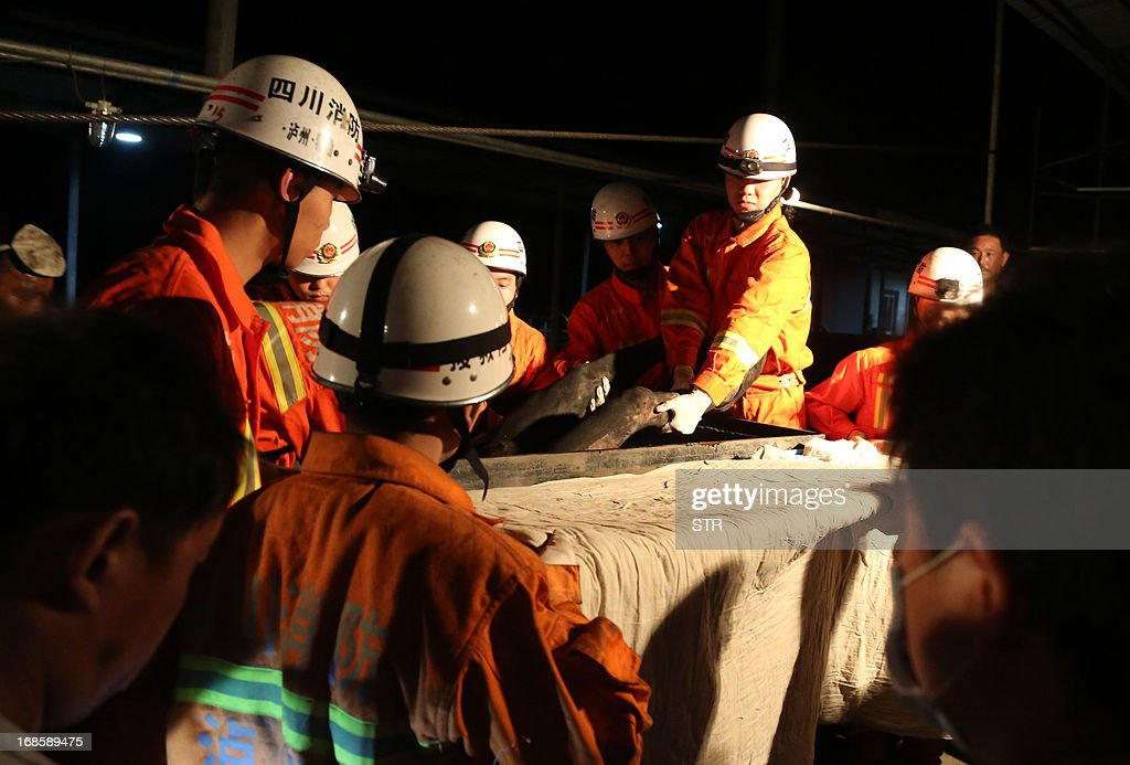 This picture taken on May 11, 2013 shows rescuers carrying a victim from the Taozigou mine in Luzhou city, Sichuan Province. An accidental explosion at a coal mine in southwest China killed 27 miners on May 11, state media said, in the second deadly incident to hit the country's troubled industry in as many days. CHINA