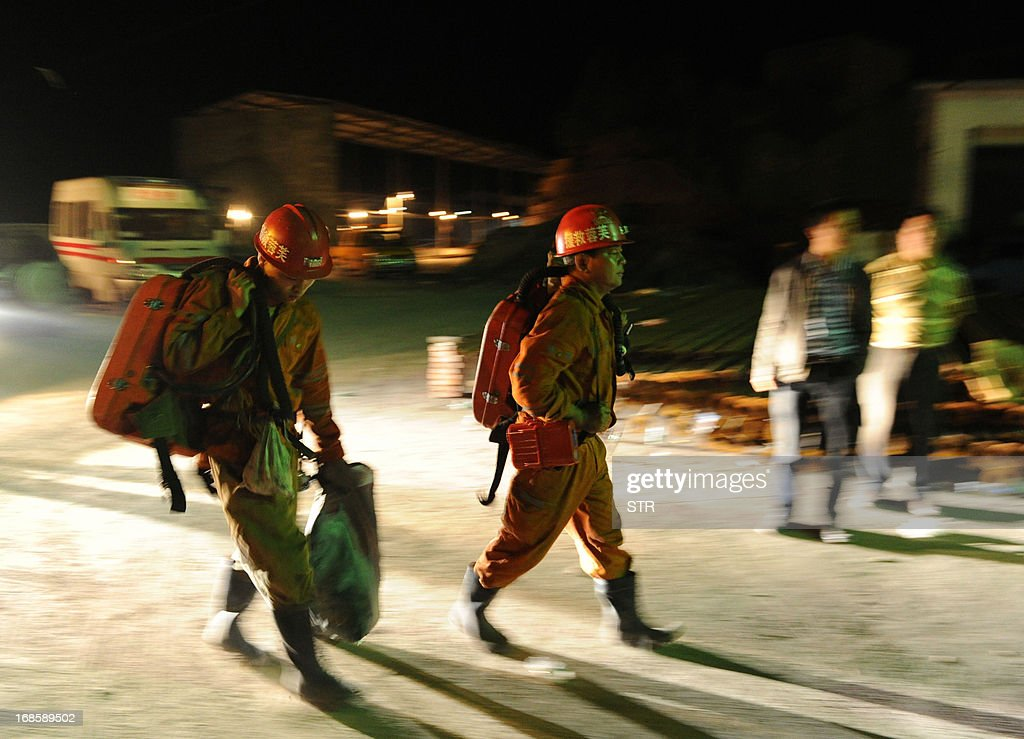 This picture taken on May 11, 2013 shows rescuers carrying equipment in Taozigou mine in Luzhou city, Sichuan Province. An accidental explosion at a coal mine in southwest China killed 27 miners on May 11, state media said, in the second deadly incident to hit the country's troubled industry in as many days. CHINA