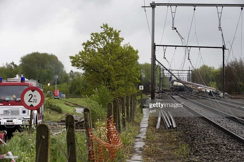 This picture taken on May 12, 2013 shows firemen still at work on the wrecked train in Wetteren on May 11, 2013. IHundreds of people evacuated from their homes after a train carrying highly toxic chemicals derailed and exploded last week are still unable to return. The accident on May 5 sent flames shooting into the sky near the city of Ghent, about 60 kilometres (40 miles) northwest of Brussels. The train contained the chemical product acrylonitrile, a toxic and inflammable fluid that can cause breathing problems. Emergency services evacuated some 2000 residents. One local resident died and in a week, 397 persons were brought to hospital, for intoxication and control. AFP PHOTO / POOL via BELGA - NICOLAS