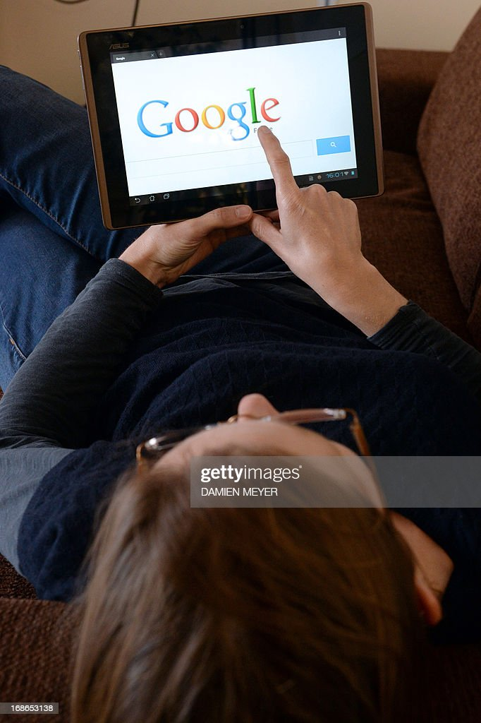 This picture taken on May 13, 2013 in the French western city of Rennes shows a woman choosing Google Search (or Google Web Search) web search engine front page on her tablet. A report by a French expert panel published on May 13, 2013 recommended imposing taxes on smartphones and tablets but rejected a call for search engine Google to be charged for linking to media content. The nine-member panel, headed by respected journalist and businessman Pierre Lescure, said in the keenly awaited report that the revenue gained from the proposed new taxes could help fund artistic and creative ventures.
