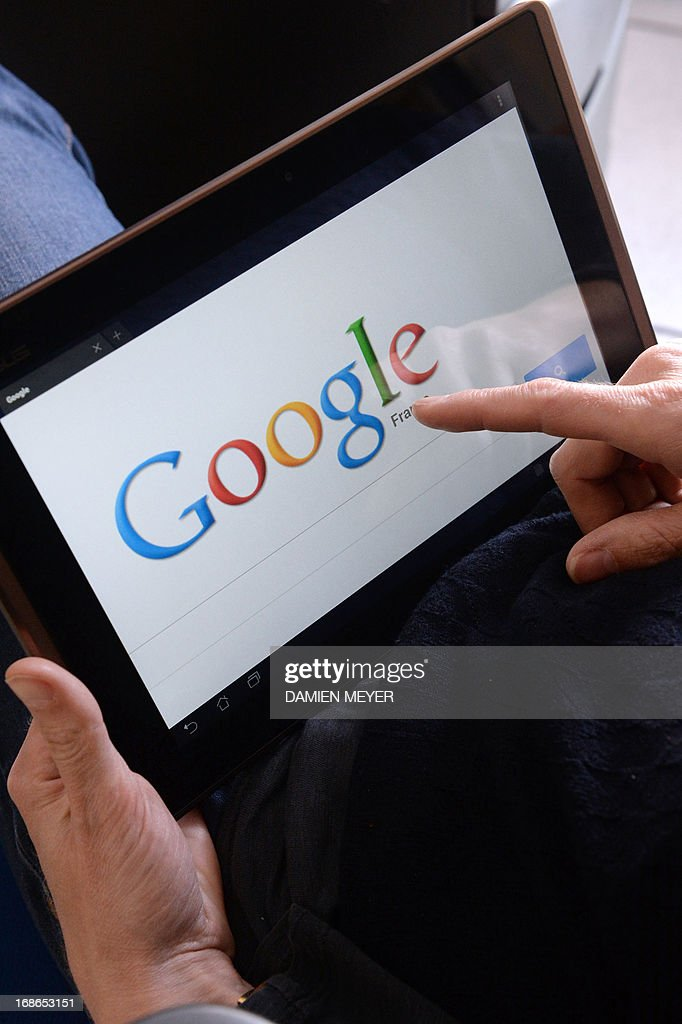This picture taken on May 13, 2013 in the French western city of Rennes shows a woman choosing Google Search (or Google Web Search) web search engine front page on her tablet. A report by a French expert panel published on May 13, 2013 recommended imposing taxes on smartphones and tablets but rejected a call for search engine Google to be charged for linking to media content. The nine-member panel, headed by respected journalist and businessman Pierre Lescure, said in the keenly awaited report that the revenue gained from the proposed new taxes could help fund artistic and creative ventures. AFP PHOTO / DAMIEN MEYER