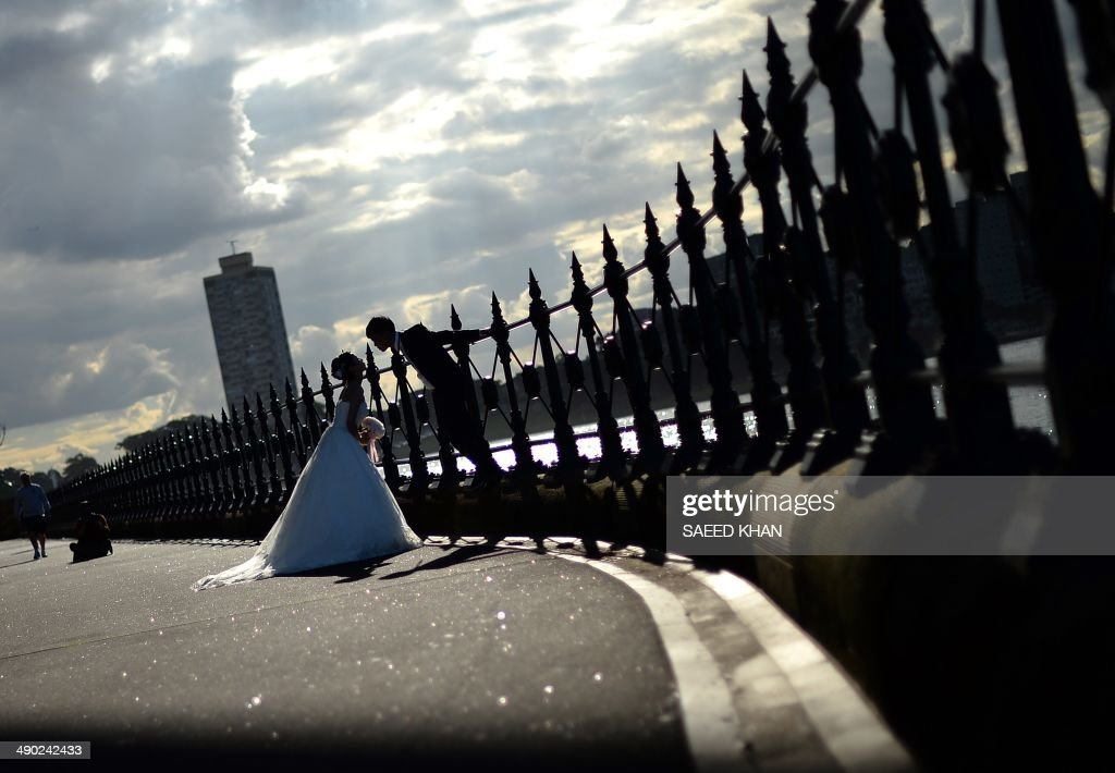 This picture taken on May 13, 2014 shows a bride and groom posing under the Sydney's iconic land mark Harbour Bridge during their photo shoot. Sydney's most popular reception venues as well as iconic land marks always attract couples for their wedding photo shoots. AFP PHOTO / Saeed KHAN