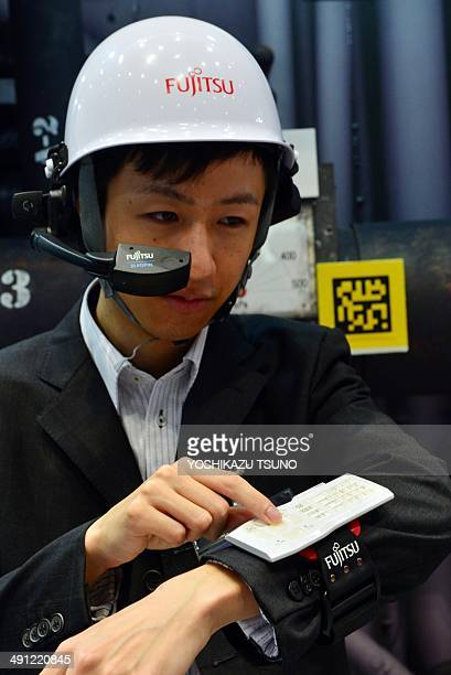 This picture taken on May 13 2014 shows an employee of Japan's computer giant Fujitsu demonstrating wearable devices for factory work at a press...