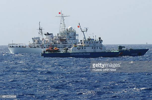 This picture taken on May 14 2014 shows a Chinese coast guard ship sailing next to a Vietnamese coast guard vessel near China's oil drilling rig in...