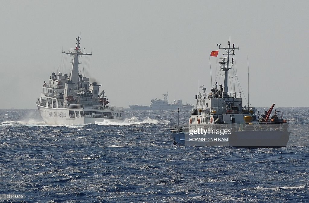 This picture taken on May 14 2014 shows a Chinese coast guard vessel followed by a Vietnamese coast guard ship near the area of China's oil drilling...
