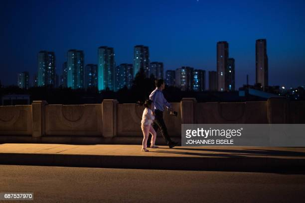 This picture taken on May 16 2017 shows a man and young girl walking over a bridge in the suburbs of Shanghai / AFP PHOTO / Johannes EISELE