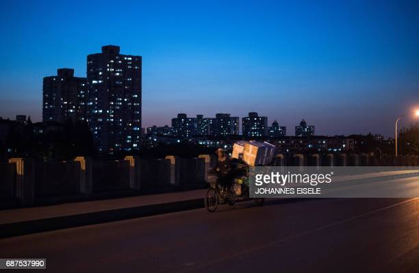 This picture taken on May 16 2017 shows a man on a tricycle riding over a bridge in the suburbs of Shanghai / AFP PHOTO / Johannes EISELE