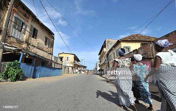 This picture taken on May 17 2012 shows women walking in a street in GrandBassam a historical town 40 km east of Abidjan threatened by coastal...