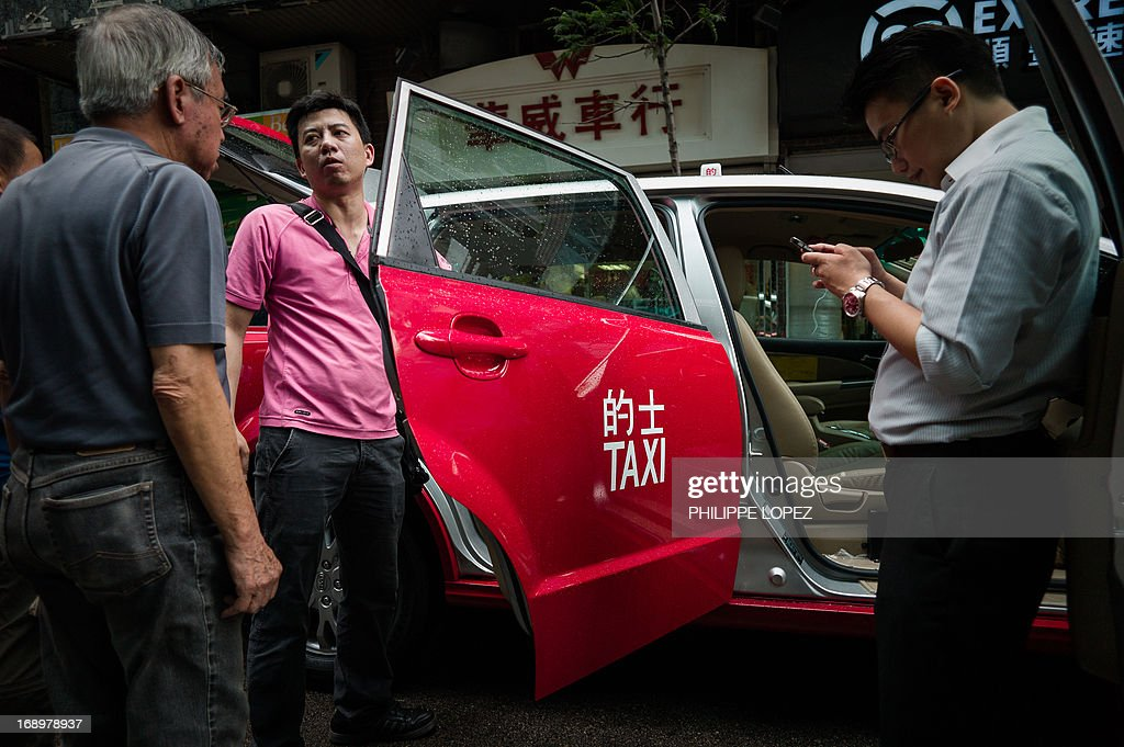 This picture taken on May 17, 2013 shows an electric taxi in street of Hong Kong. Hong Kong saw its first electric taxis hit the streets on May 18 in a step towards reducing the city's high levels of roadside pollution. The 45 bright red cars were launched by Chinese electric vehicle producer BYD, which is partly backed by US investment titan Warren Buffett. AFP PHOTO / Philippe Lopez
