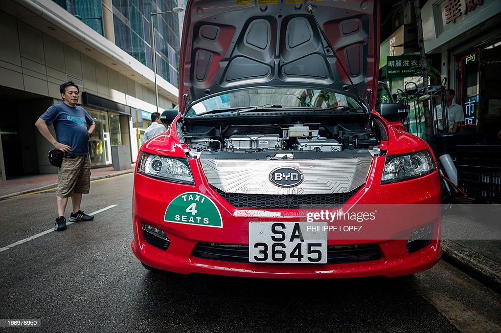 This picture taken on May 17, 2013 shows an electric taxi on a street in Hong Kong. Hong Kong saw its first electric taxis hit the streets on May 18 in a step towards reducing the city's high levels of roadside pollution. The 45 bright red cars were launched by Chinese electric vehicle producer BYD, which is partly backed by US investment titan Warren Buffett. AFP PHOTO / Philippe Lopez