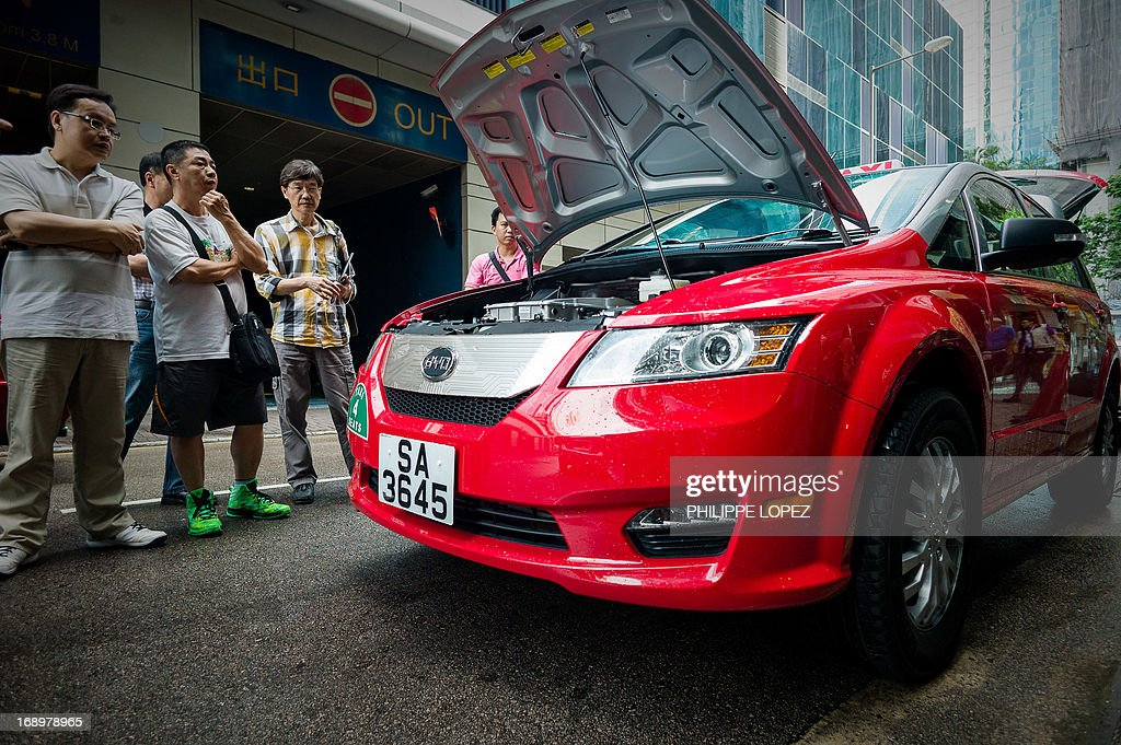 This picture taken on May 17, 2013 shows people looking at an electric taxi on a street in Hong Kong. Hong Kong saw its first electric taxis hit the streets on May 18 in a step towards reducing the city's high levels of roadside pollution. The 45 bright red cars were launched by Chinese electric vehicle producer BYD, which is partly backed by US investment titan Warren Buffett. AFP PHOTO / Philippe Lopez