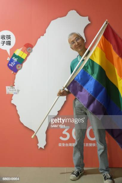 This picture taken on May 19 2017 shows Taiwanese gay rights campaigner Chi Chiawei posing for a photograph with a flag during an exhibition in...