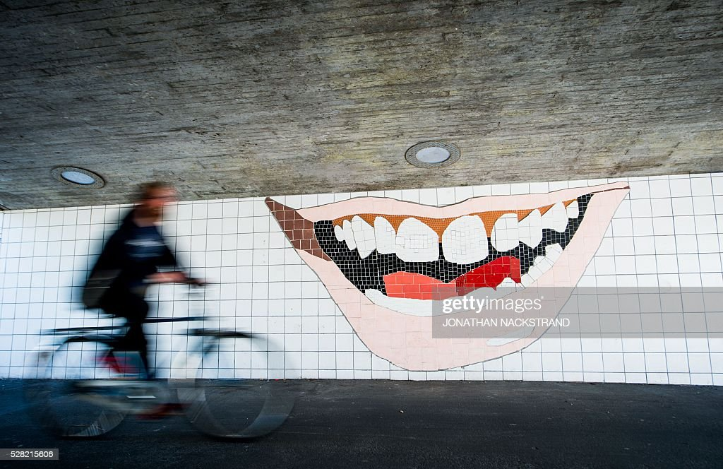 This picture taken on May 2, 2016 in the neighbourhood of Rosengard in Malmoe, where Swedish national team football player, Zlatan Ibrahimovic grew up, shows a cyclist next to a mosaic in the shape of Zlatan's smile. / AFP / JONATHAN