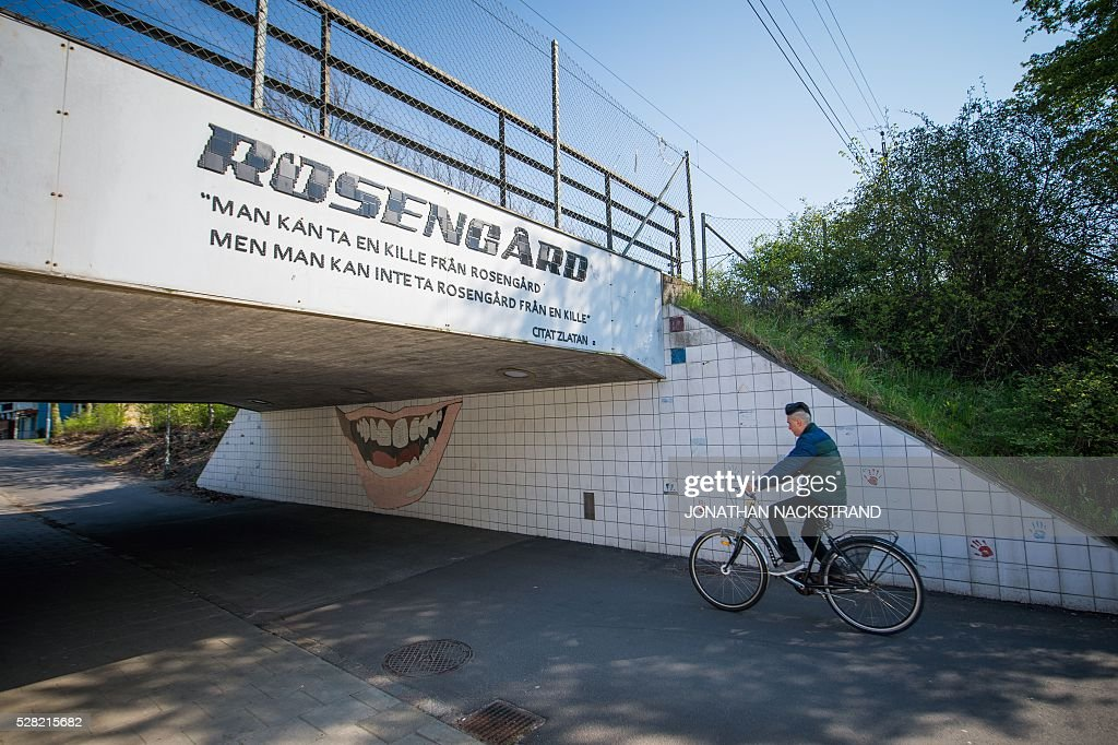 This picture taken on May 2, 2016 in the neighbourhood of Rosengard in Malmoe, where Swedish national team football player, Zlatan Ibrahimovic grew up, shows a cyclist next to a mosaic in the shape of Zlatan's smile under a bridge with a quote from Ibrahimovic 'You can take a men from Rosengard but you can't take Rosengard from a men'. / AFP / JONATHAN