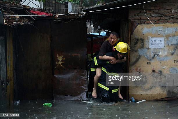 This picture taken on May 20 2015 shows rescuers helping a resident through a flooded area during an intense rainstorm that killed 7 people in Xiamen...