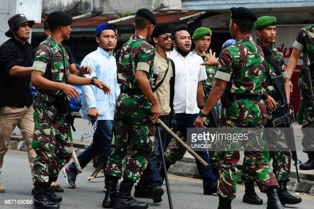This picture taken on May 20 2017 shows members of a hardline Indonesian Muslim group holding wooden sticks during a local tribal festival in...