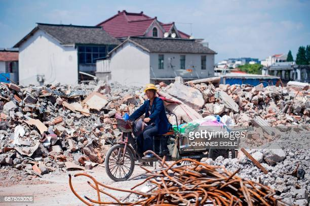 TOPSHOT This picture taken on May 22 2017 shows a migrant worker on her tricycle at the demolition site of the Jiuxing furniture market in the...
