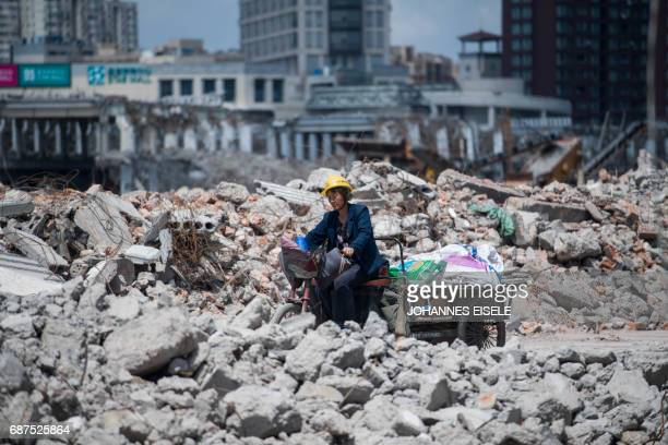 This picture taken on May 22 2017 shows a migrant worker on her tricycle at the demolition site of the Jiuxing furniture market in the suburbs of...