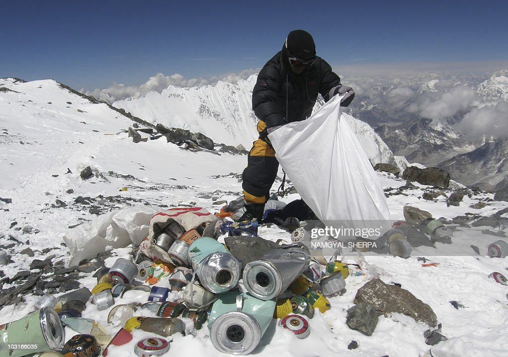 This picture taken on May 23, 2010 shows a Nepalese sherpa collecting garbage, left by climbers, at an altitude of 8,000 metres during the Everest clean-up expedition at Mount Everest. A group of 20 Nepalese climbers, including some top summiteers collected 1,800 kilograms of garbage in a high-risk expedition to clean up the world's highest peak. Led by seven-time summiteer Namgyal Sherpa, the team braved thin air and below freezing temperatures to clear around two tonnes of rubbish left behind by mountaineers, that included empty oxygen cylinders and corpses. Since 1953, there have been some 300 deaths on Everest. Many bodies have been brought down, but those above 8,000 metres have generally been left to the elements -- their bodies preserved by the freezing temperatures. The priority of the sherpas had been to clear rubbish just below the summit area, but coordinator Karki said large quantities of refuse was collected from 8,000 meters and below. AFP PHOTO/Namgyal SHERPA