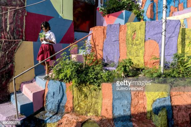 This picture taken on May 23 2017 shows a village girl walks along a path at an Indonesian hamlet dubbed 'the rainbow village' in Semarang central...