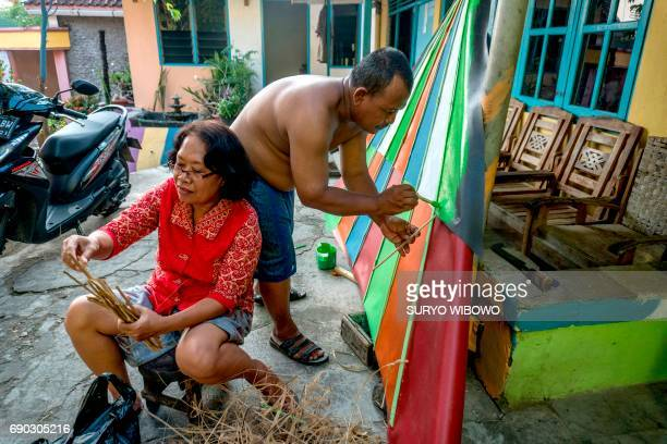 This picture taken on May 23 2017 shows villagers painting part of their homes following a major makeover of their Indonesian hamlet dubbed 'the...