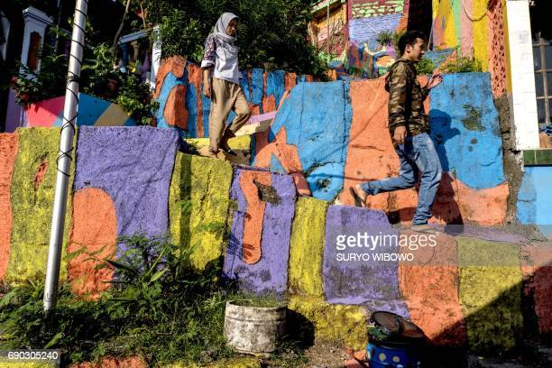This picture taken on May 23 2017 shows villagers walking along a path at an Indonesian hamlet dubbed 'the rainbow village' in Semarang central Java...