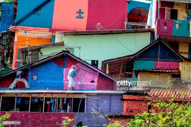 This picture taken on May 23 2017 shows workers painting houses at an Indonesian hamlet dubbed 'the rainbow village' in Semarang central Java that...