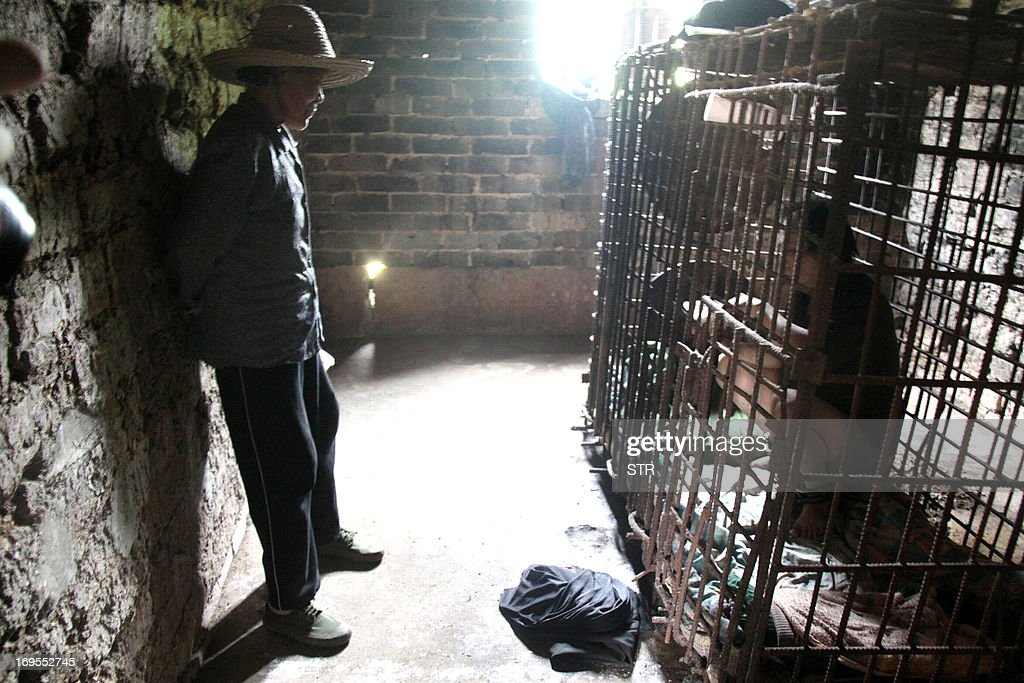 This picture taken on May 24, 2013 shows Wu Yuanhong, 42, a mentally ill Chinese man, eats his lunch in a cage, which he has been kept for more than a decade by his family, as his mother (L) looks on at their home in Lijiachong village in Ruichang, China's Jiangxi province. Yuanhong, was shown sitting on blankets in the narrow enclosure, his feet shackled with a heavy chain and wearing only a T-shirt and his underwear, as he was diagnosed as a schizophrenic at the age of 15 and in 2001 he beat a 13-year-old to death. CHINA OUT AFP PHOTO