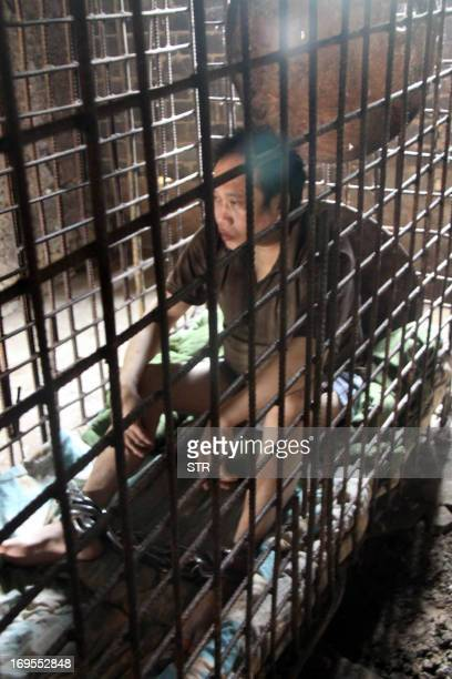 This picture taken on May 24 2013 shows Wu Yuanhong a mentally ill Chinese man sits in a cage which he has been kept for more than a decade by his...