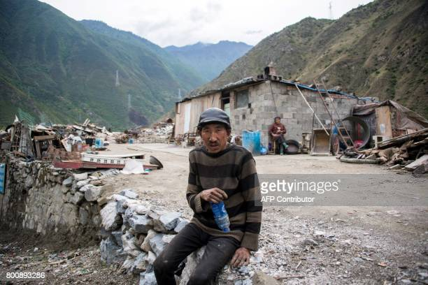 This picture taken on May 25 2017 shows a man sitting next to the debris of demolished houses and a makeshift hut next to a catchment lake near...