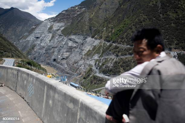This picture taken on May 25 2017 shows a man sitting on a wall next to the construction site of the Lianghekou dam near Hekou in Sichuan province...