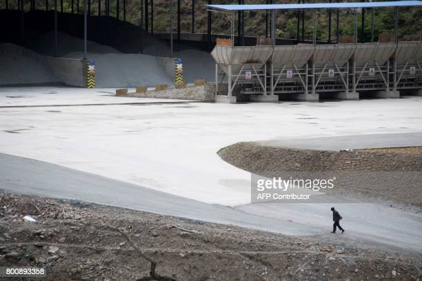 This picture taken on May 25 2017 shows a man walking near a cement factory near the dam in Lianghekou Towering walls of concrete entomb lush forests...