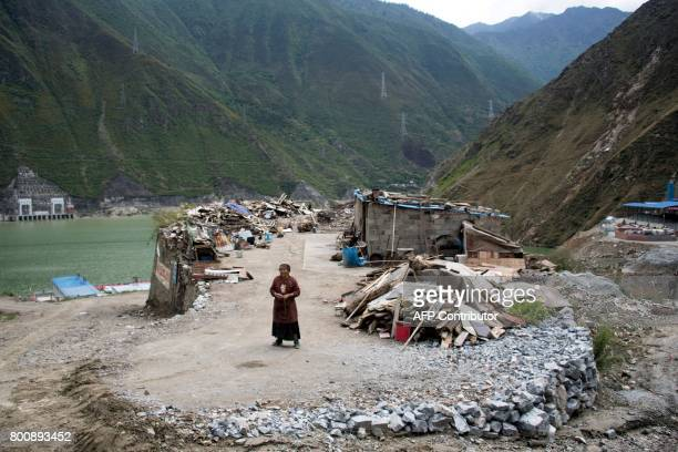 This picture taken on May 25 2017 shows a woman standing next to the debris of demolished houses and her makeshift hut next to a catchment lake near...