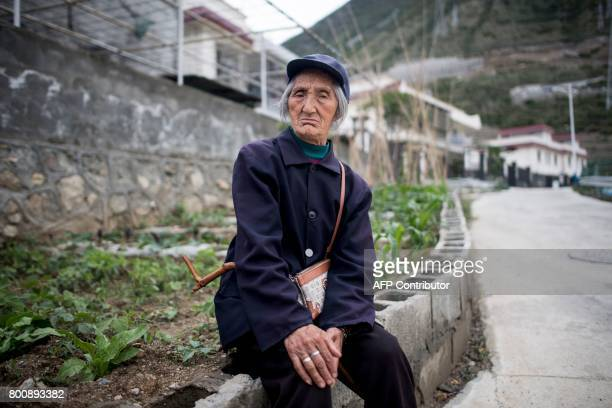 This picture taken on May 25 2017 shows Gu Huafei sitting on a low wall in a new village near Lianghekou after being relocated due to the...