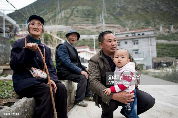 This picture taken on May 25 2017 shows Gu Huafei sitting on a wall with other villagers in a new village near Lianghekou after they were relocated...