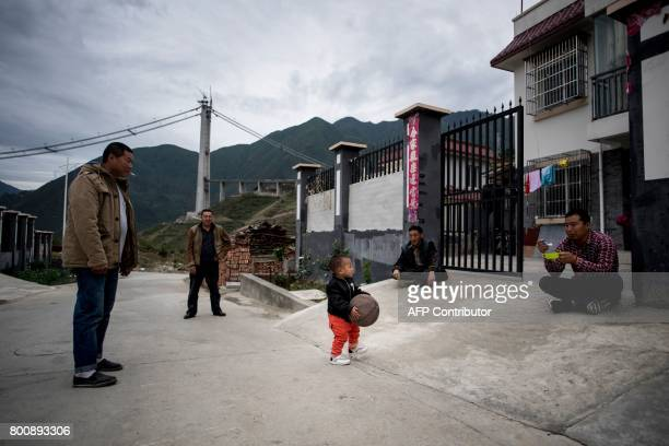 This picture taken on May 25 2017 shows villagers playing with a child in a new village near Lianghekou after they were relocated due to the...